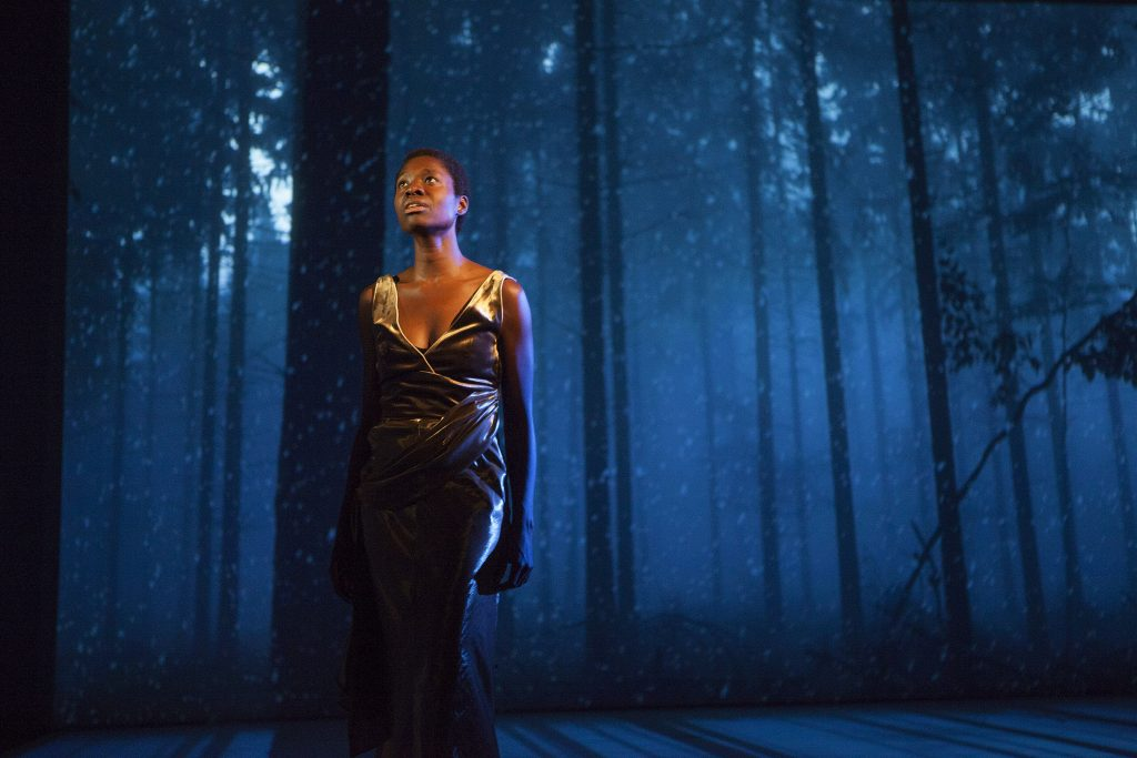 A woman stands on stage with a projection behind her of a blue forest