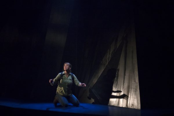 A woman kneels on a mountain on a stage