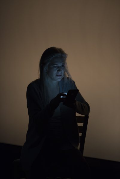 a blond woman holds a cell phone