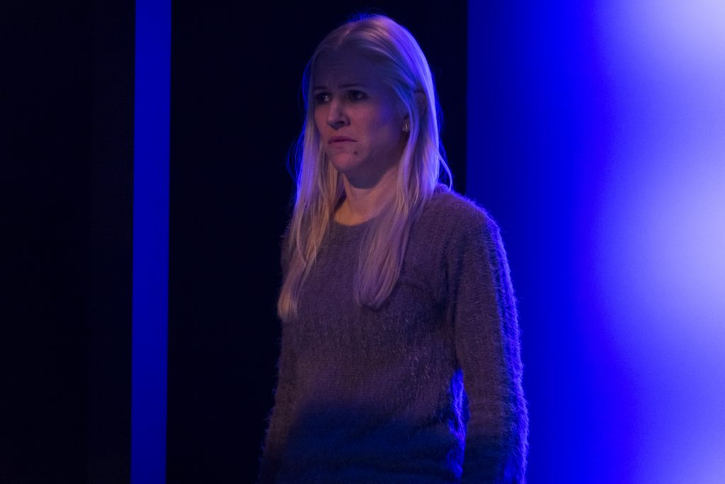 A woman stands in front of a glowing blue wall in a play