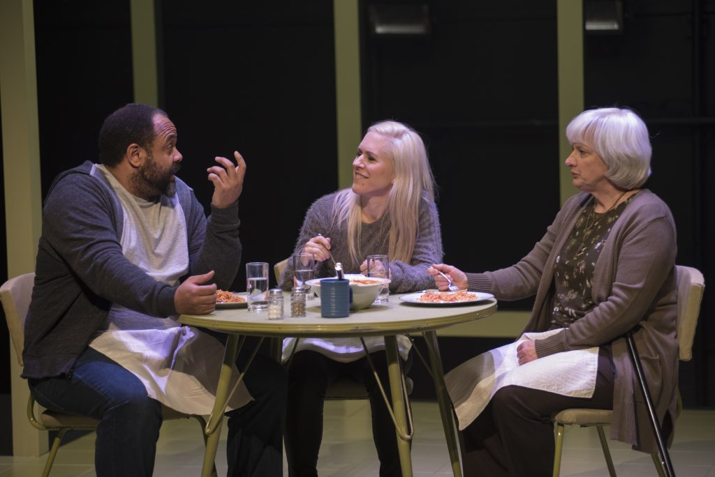 three people sit at a table in a play eating