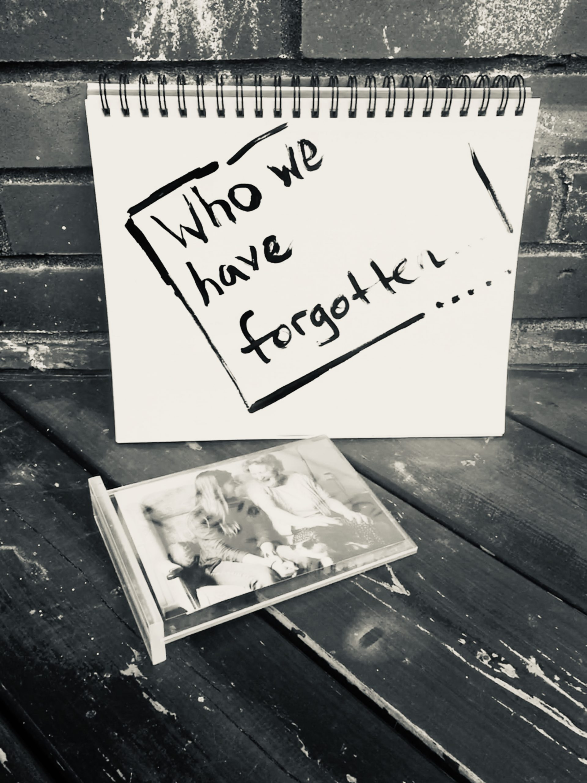 """A sign reads """"Who Have We Forgotten?"""""""