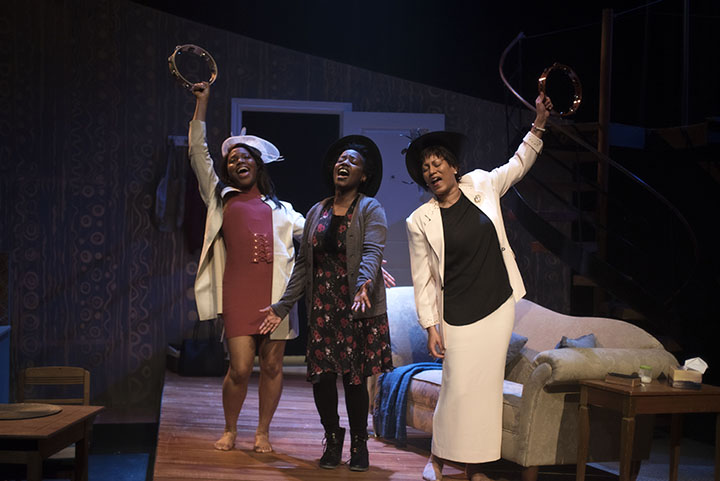 Three black women wearing hats hold their arms in the air and shake tambourines
