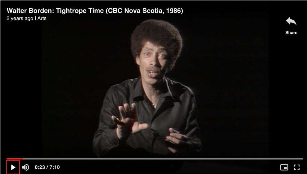 A man in a black shirt with an afro is addressing the camera in mid-speech