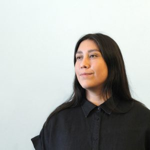 A woman with long straight black hair wears a black button down short sleeve shirt on a white background