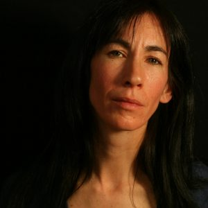 A close up of a woman with dark hair on a black background