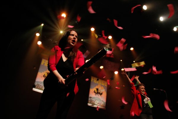 A woman with brown hair shoots out confetti from on stage