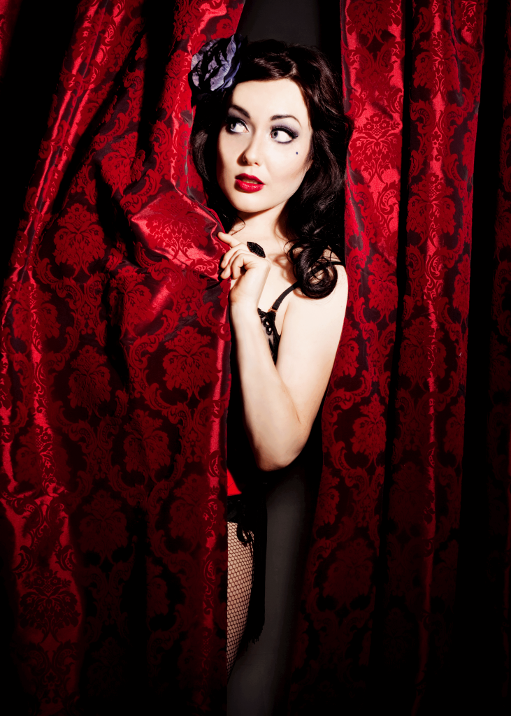 An unclothed woman peeks out from behind a red velvet curtain.