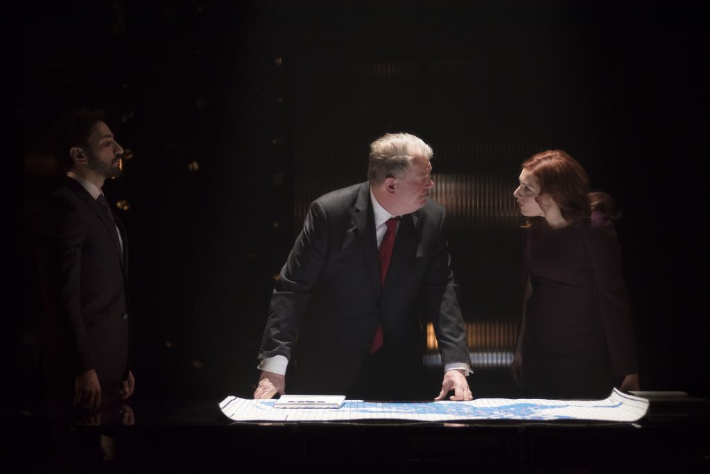 Henry VIII and Katharine Parr in modern costume stand over unfurled map.