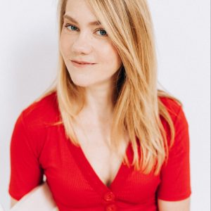 Amelia has blond hair and wears a red shirt. She is seated on a white wooden chair and looks out at you with a small grin, perhaps a bit impishly.