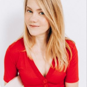 Amelia has blond hair and wears a red shirt. SHe is seated on a whit wooden chair and looks out at you with a small grin, perhaps questioningly..