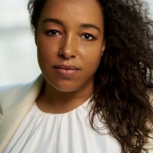 A close up photo of a woman with black curly hair wearing a white shirt.