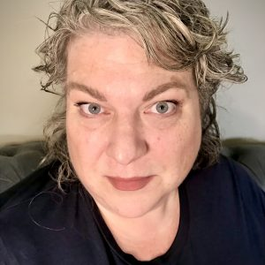 Close up photo of a woman's face. She has short blond, wavy hair and wears a black shirt.