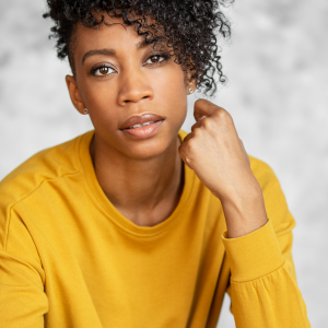 Close up photo from the waist up of a woman with black curly hair wearing a mustard coloured long sleeve shirt