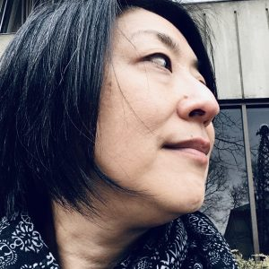 A profile of a woman's face. She has chin length straight black hair.